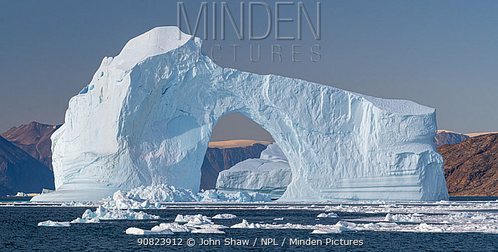 Iceberg with arch in Hall Bredning, Scoresby Sund, Greenland, August.