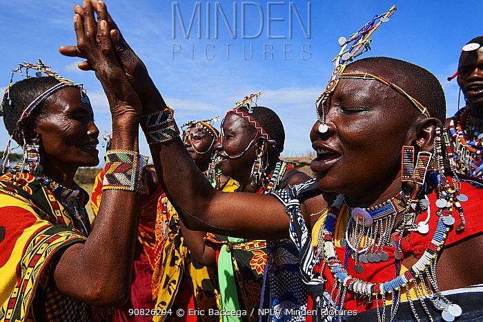 Group of Maasai women singing and dancing in traditional dress and adorned with bead work, Masai Mara National Reserve, Kenya.
