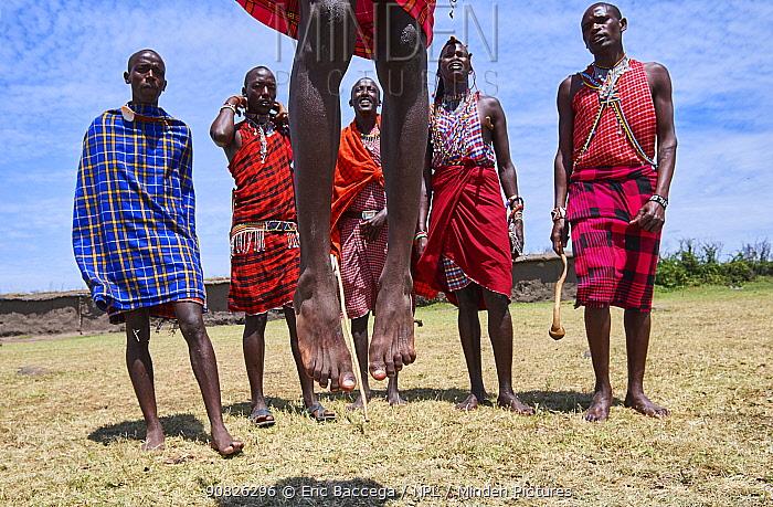 Young Maasai men performing a traditional jumping dance, Masai Mara National Reserve, Kenya.