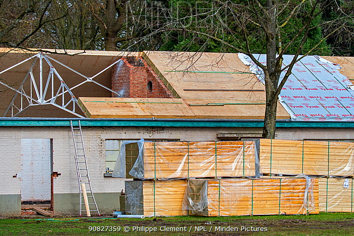 Building fitted with warm pitched roof insulation by installing insulating sandwich panels, Belgium, March 2019.