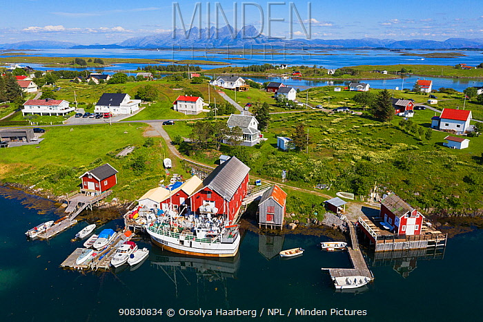 Aerial view of an island far out in the sea in Norway's widest strandflat. Fishing village with boats and boat houses. Brasoya, Helgeland Archipelago, Norway. July.
