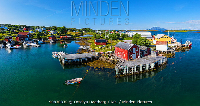 Aerial view of an island far out in the sea in Norway's widest strandflat. Fishing village with boats and boat houses. Husvaer, Helgeland Archipelago, Norway. July.