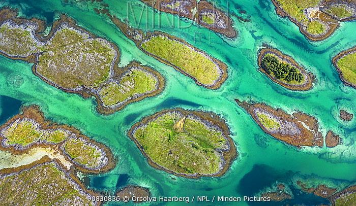 Aerial view of sporadically inhabited islands, islets and skerries in a wide coastal plain. Husvaer, Helgeland Archipelago, Norway. July.
