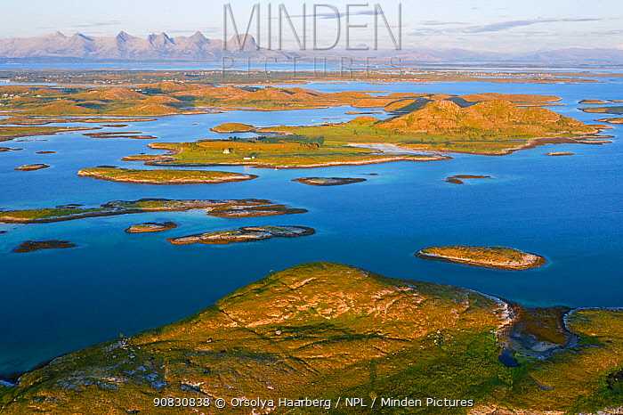 Aerial view of sporadically inhabited islands, islets and skerries, illuminated by the warm evening light. Landmark mountain the Seven Sisters can be seen in the background. Oksningan, Heroy, Helgeland Archipelago, Norway. July.