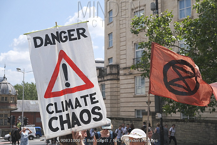 'Danger climate chaos' placard and Extinction Rebellion flag. Climate change protest march, Bristol, England, UK. 16 July 2019.
