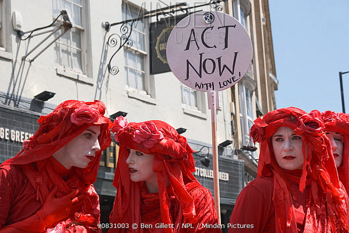 The Red Brigade performance artists with 'Act Now with love!' placard. Extinction Rebellion climate change protest, Bristol, England, UK. 16 July 2019.