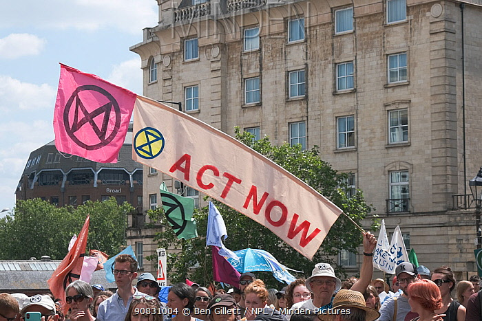 'Act now' banner and Extinction Rebellion flag held aloft during climate change protest march. Bristol, England, UK. 16 July 2019.