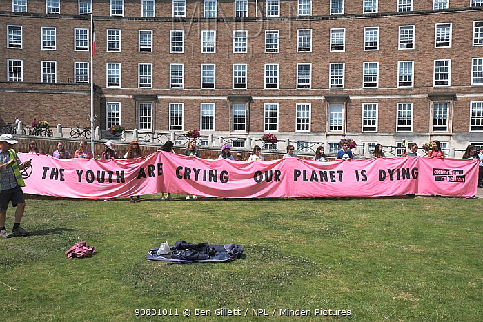 School children holding 'The youth are crying our planet is dying' banner at Extinction Rebellion march and rally. Bristol, England, UK. 16 July 2019.