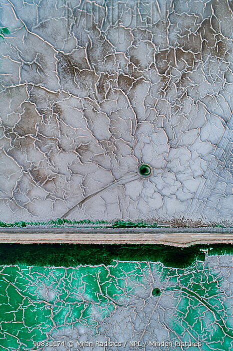 Service road crossing an abandoned pond used for the disposal and stacking of phosphogypsum with crystallised patterns and shallow, but highly toxic radioactive green water in Huelva, Southern Spain. Phosphogypsum is a radioactive by-product in the manufacture of phosphoric acid, used for phosphate-based fertilizers.
