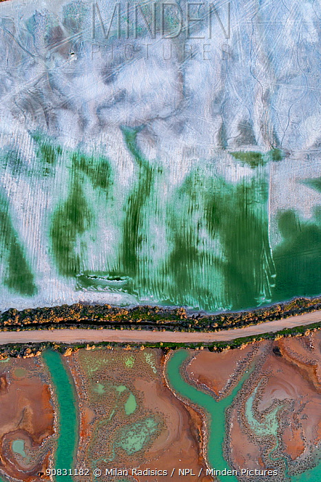 Coloured water leaking from photogypsum storage pond creates tidal channels in saltmarsh habitat. Huelva, Southern Spain. Phosphogypsum is a radioactive by-product in the manufacture of phosphoric acid, used for phosphate-based fertilizers.