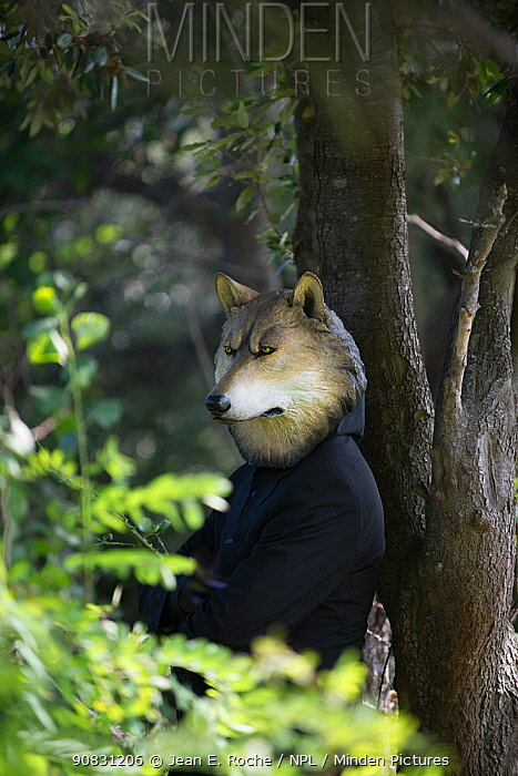 A man in a wolf mask leaning against a tree with his arms crossed, from the 'Les souffleurs, commando po�tique' company, Festival 'Les Envies Rh�nements' 2018. Camargue, France.