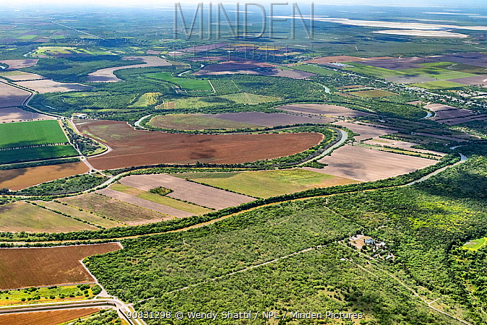 Aerial view of border wall at Southmost Preserve, Texas, USA. 85% of the reserve lies on the no-man's land side between the wall and the Rio Grande river disrupting The Nature Conservancy's activities and movement of wildlife. Fields on other side of river in Tamaulipas, Mexico. July 2017.