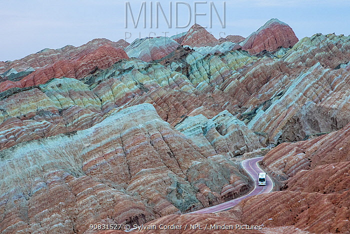 Tourist bus on winding road through eroded hills of sedimentary conglomerate and sandstone. Rainbow Mountains, Zhangye National Geopark, China Danxia UNESCO World Heritage Site, Gansu Province, China. 2018.