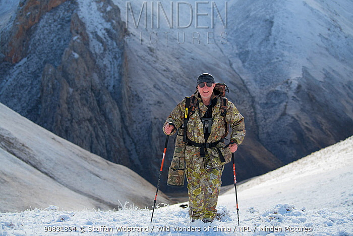 Wildlife photographer Staffan Widstrand hiking on snow covered mountain slope. Valley of the Cats, Angsai Nature Reserve, Sanjiangyuan National Nature Reserve, Tibetan Plateau, Qinghai, China. October 2019.