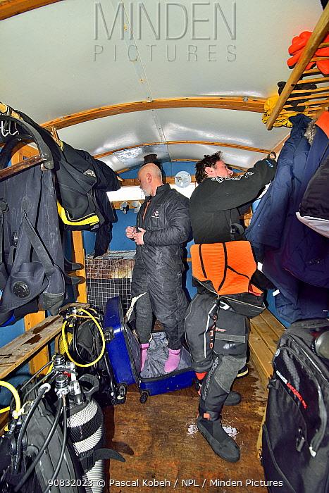 Divers preparing to dive on ice field. Karelia, Russia. White Sea.