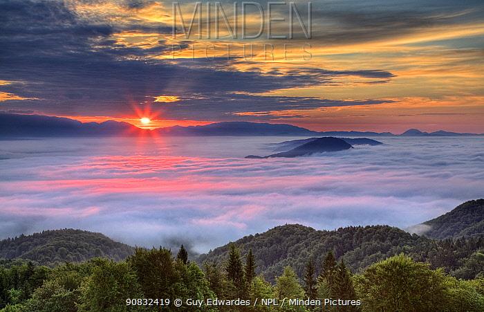 Sunrise with dawn over mist shrouded Ljubljana Basin, Grmada Hill, Tehovec, Slovenia, June 2008.