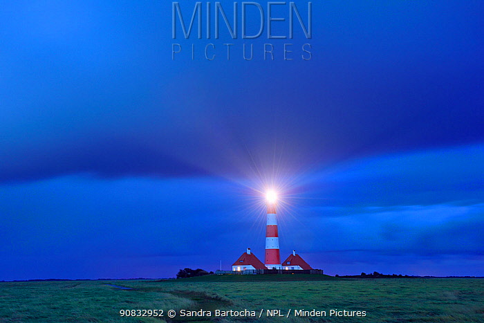 Westerhever lighthouse at dusk with light on, St. Peter Ording, Schleswig-Holstein Wadden Sea National Park, Germany, September.