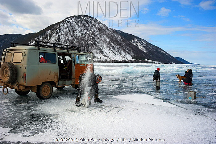 People digging a square hole through thick ice for ice diving, Lake Baikal, Siberia, Russia, April 2016.