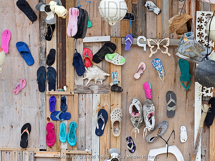 Plastic rubbish, mainly shoes, washed ashore and used to decorate wall, Wizard Island, Cosmoledo Atoll, Seychelles