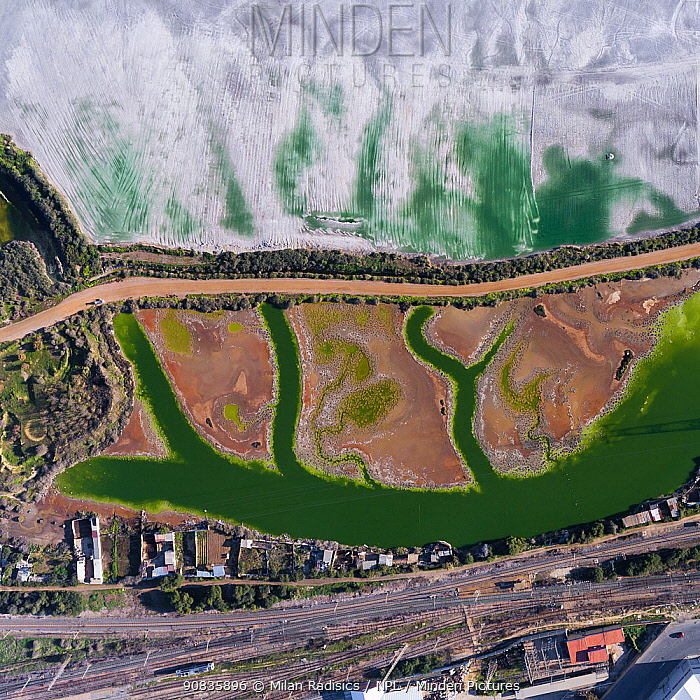 Coloured water leaking from photogypsum storage pond creates tidal channels in saltmarsh habitat. Huelva, Southern Spain. Railway lines pass nearby. Phosphogypsum is a radioactive by-product in the manufacture of phosphoric acid, used for phosphate-based fertilizers.