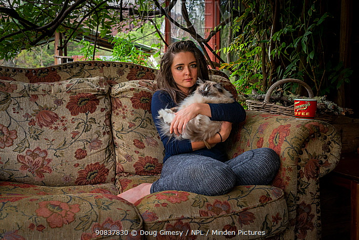 Emily Small,one of the founders of the Goongerah Wombat Orphanage, sits on the veranda of her house, with her ragdoll cat Cotton', shortly after the 2019/20 bushfires devastated the area. Emily's house was spared, but she lamented the loss of her surrounding home. ?Goongerah, Victoria, Australia. February, 2020. Editorial use only.