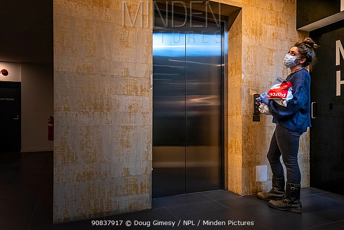 Emily Small, founder of Goongerah Wombat Orphanage, wildlife rescuer and carer, taking the lift up to her Melbourne inner city apartment during the CoVid-19 lockdown.Preston, Victoria, Australia, July, 2020. Editorial use only,