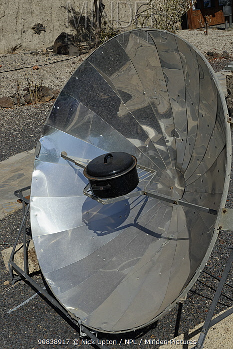 Solar cooker, with a reflective parabolic dish focusing heat from the sun onto a metal casserole pot, within a renewable energy display at ITER Bioclimatic village, near El Medano, Tenerife, August.