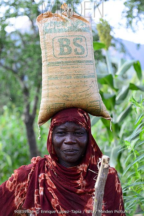 Hadjarai woman, carrying a large sack balanced on head, Moukoulou village. South Chad. September 2019.