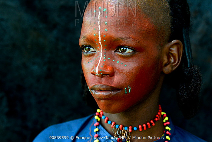 Boy from Wodaabe nomadic tribe with painted face, portrait. During Gerewol celebration, a gathering of different clans in which women choose a husband. Chad, Sahel, Africa. 2019.