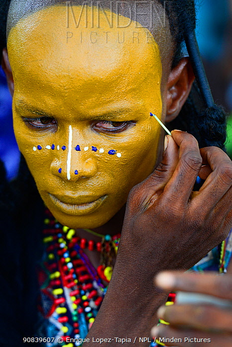 Man from Wodaabe ethnic group painting face for Gerewol celebration, a gathering of different clans in which women choose a husband. Men dress in best clothes and ornaments and sing and parade in front of the young women. Chad, Sahel, Africa. 2019.