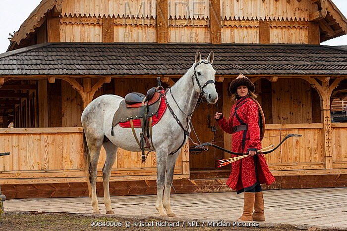 Cossack woman standing with Akhal-Teke horse in front of wooden building at Kievan Rus Park, a reconstruction of the former capital Rus. Ukraine, 2020.