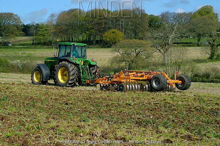 John Deere tractor with a Simba power disc harrow cultivating set-a-side field before planting with maize in Devon, April