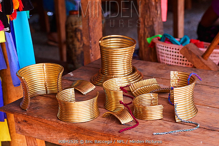 False brass neck rings for tourists. Either you clip two parts to have a full collar or you adjust one single part with cords around you neck. In the background a real brass neck coil (approx. 3 kg ). The tourist shops are held by Kayan Lahwi women. The Long Neck Kayan (also called Padaung in Burmese) are a sub-group of the Karen ethnic people from Burma. They wear spiral coils around their neck and lower legs.They are also nicknamed 'giraffe women'. PanPet tourist market, Kayah state, Myanmar April 2019.