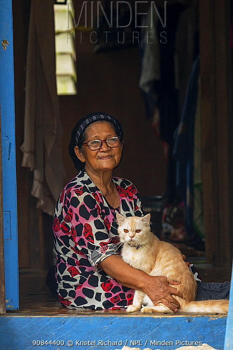 Local woman sitting in her home with her cat in her lap, Kinabatangan River, Sabah, Borneo, Malaysia. Endangered species.