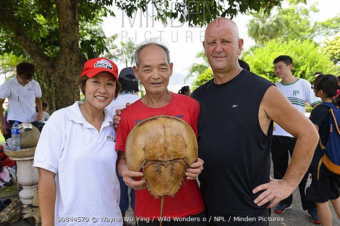Man holding Horseshoe crab (Tachypleus tridentatus) at Horseshoe crab release event oragnized by Ocean Park Conservation Foundation, Hak Pak Nai beach, Yue Long, Hong Kong, China