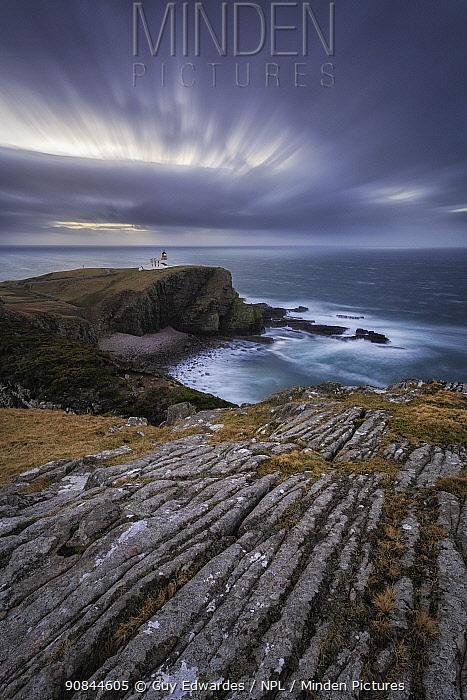 View across rocky cliffs to Stoer Lighthouse. Assynt, Sutherland, Highland, Scotland, UK. January