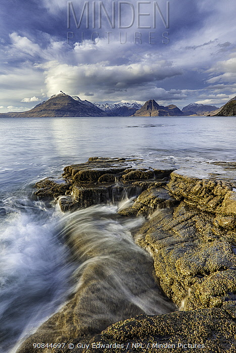 Tide passing over rocks on shore, view across sea to Black Cuillins. Elgol, Isle of Skye, Scotland, UK