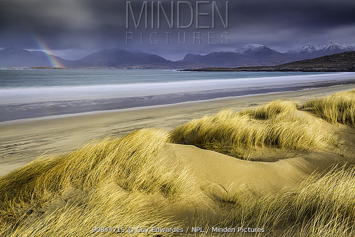Sand dunes and beach under stormy sky, rainbow in distance. Luskentyre, Isle of Harris, Outer Hebrides, Scotland. March 2015.