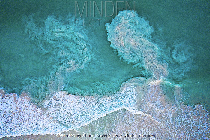 Aerial view of waves crashing on a beach and carrying sediments back out to sea. The Bahamas.