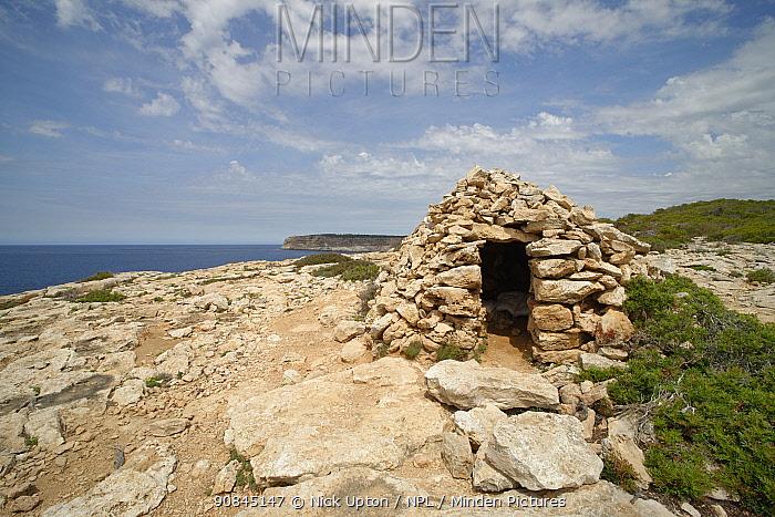 Shepherd's refuge built of stone on by coastal path along high limestone clifftops between Cala Pi and Cap Blanc, near Llucmajor, Mallorca south coast, May 2019.