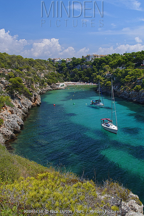 Yachts moored in the cove at Cala Pi, viewed from narrow cliff top coast path, Mallorca south coast, August 2018.