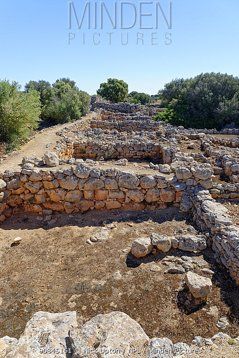 Ruins of ancient stone houses at Capocorb Vell, a much excavated settlement built by the Talaiotic culture, which flourished in Mallorca between around 1300 and 800 BC, near Cala Pi, Mallorca. May 2019.