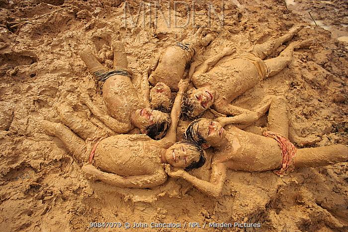 Mayoruna children playing in mud Amazonia, Peru