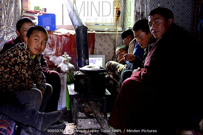 Group of novice monks sitting around stove whilst resting at Bangpu Monastery / Panphuk Gompa, Sangdui, Sichuan, China. 2016.