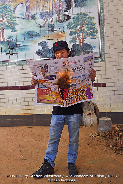 Photographer Deng with 'hot news', newspaper on fire, Zhang Jiang city, Guangdong province, China