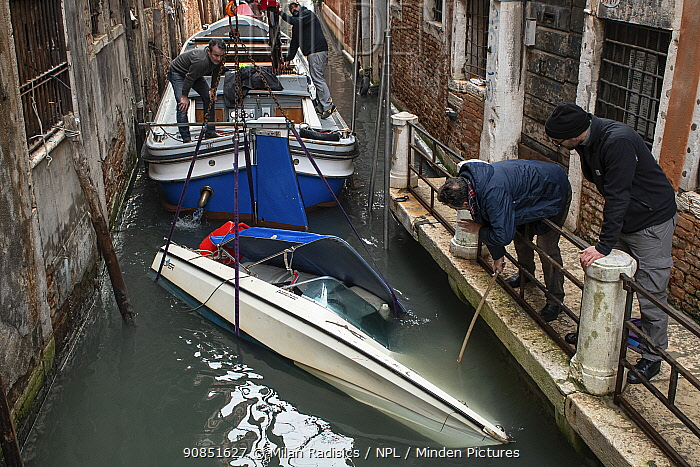 Local men recovering small capsized boat during flooding in Venice, Italy, December 2019.