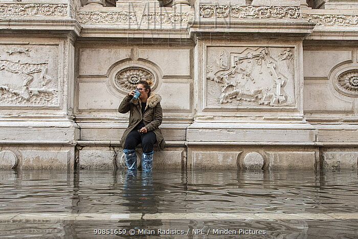 Woman in wellington boots, sitting on ledge and observing flooding in Venice, Italy, December 2019.