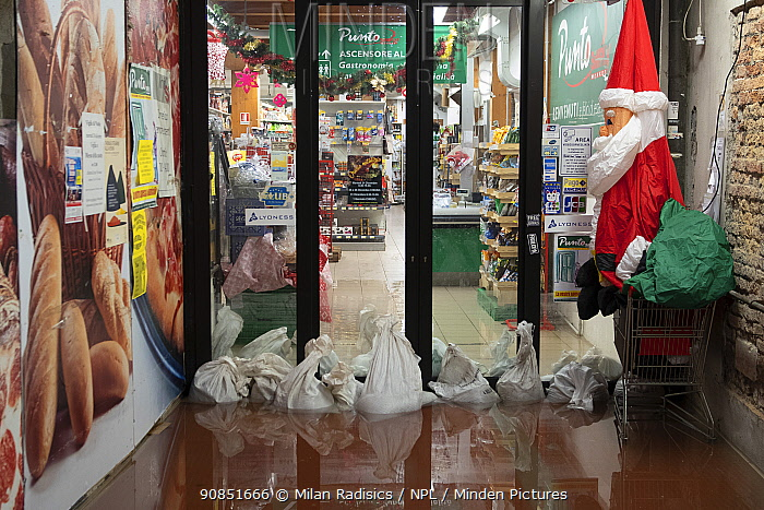 Shop with sandbags during flooding in Venice, with Father Christmas decoration, Italy, December 2019.
