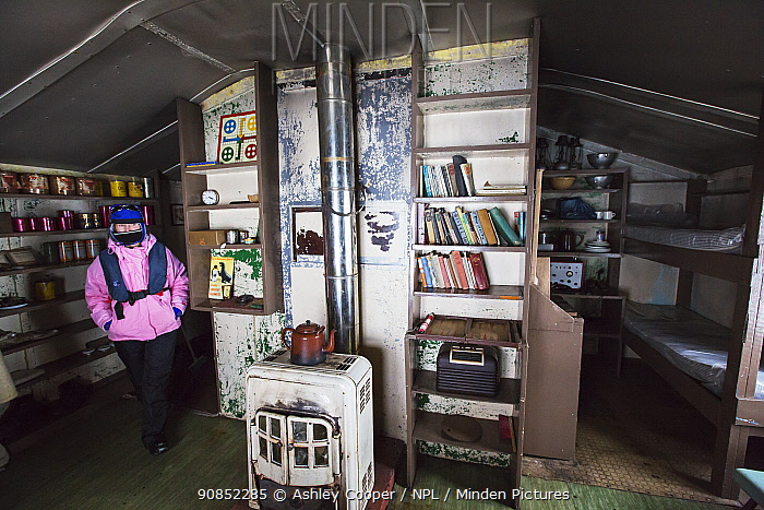 Tourist beside heating stove in Wordie House, a former British scientific research base, Winter Island, Argentine Islands, Antarctica. 2020.