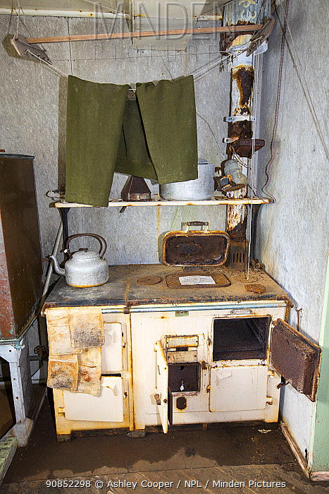 Trousers drying above kitchen stove, Station W, former British scientific research station evacuated in 1959. Detaille Island, Graham Land, Antarctica. 2020.